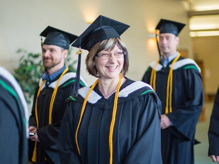 Adult students in grad gowns