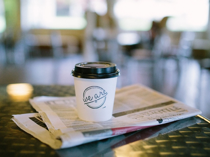 Coffee cup sitting on top of a newspaper