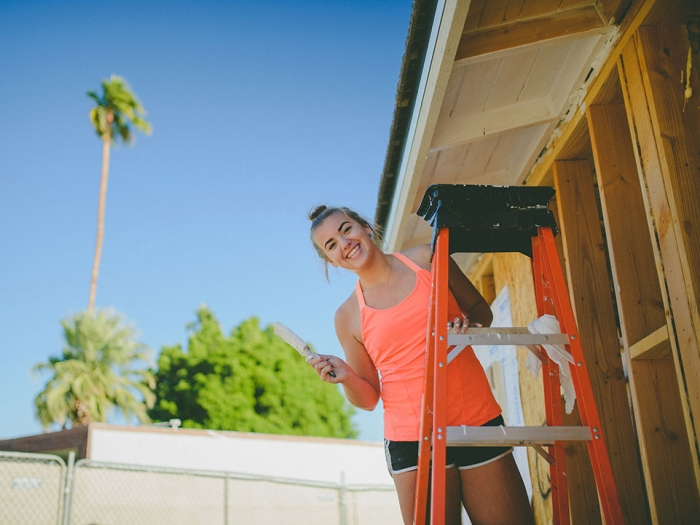 Female student posing on a ladder with a paintbrush
