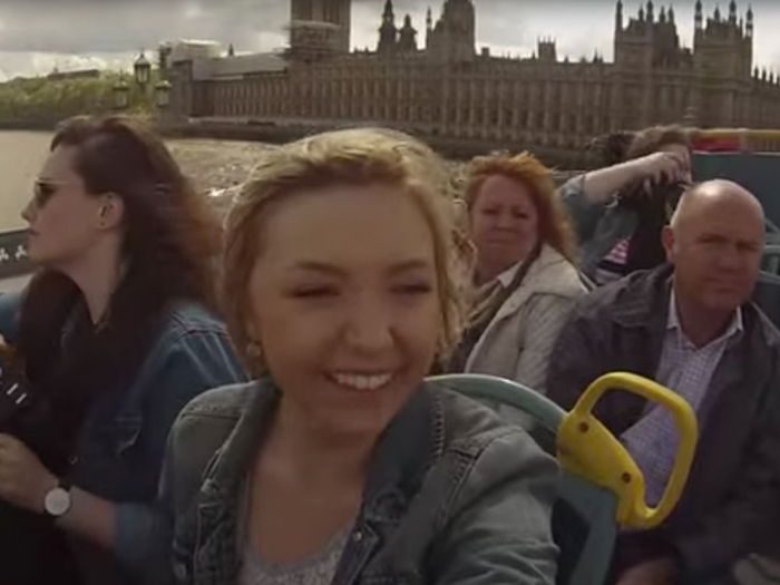 Student riding a tour bus in London