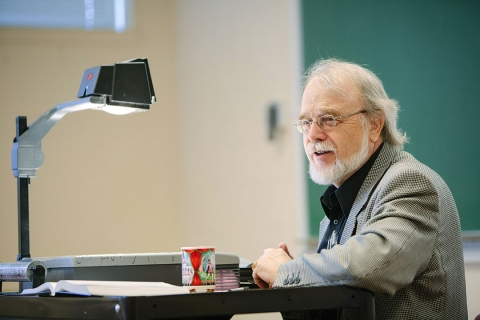 Human Services Professor leaning on projector