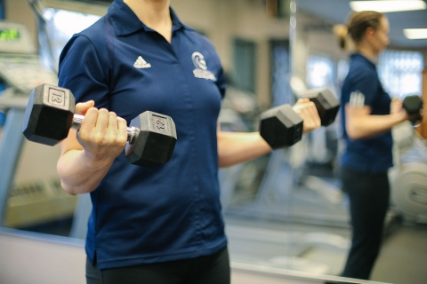 Female instructor lifting weights