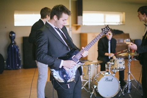 Student playing guitar with a band