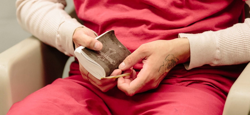 Prisoner with a Bible in lap
